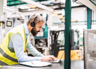 An industrial man engineer with headset and laptop in a factory, working. Wall mural