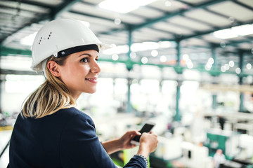 A portrait of an industrial woman with smartphone, standing in a factory.