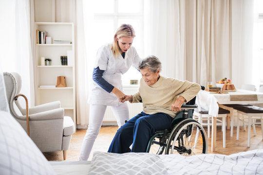 A health visitor helping a senior woman to stand up from a wheelchair.