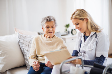 A health visitor and a senior woman sitting on a bed at home, talking. Wall mural