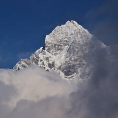 Peak of Mount Thamserku reaching out of the clouds. Nepal.