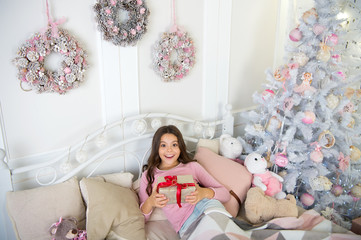 little child girl with xmas present. The morning before Xmas. Sleep. small girl relax at home. christmas family holiday. happy new year. Christmas shopping. Opening her Christmas present