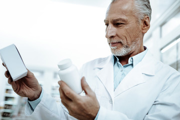 Attentive mature man choosing best tablets for recover