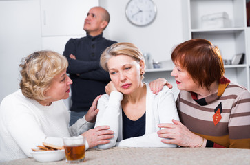 Two mature women are careing for their womanfriend who is sad