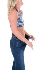 Woman shows lost weight in big jeans Isolated on white background