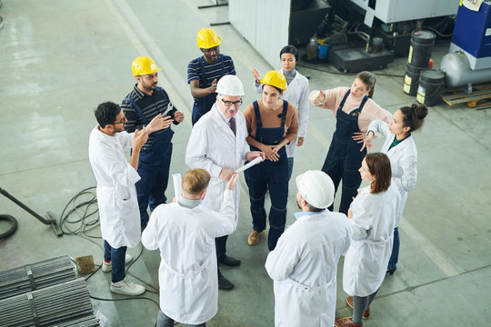 High angle view at  multi-ethnic group of workers standing round senior engineer giving instructions on project in workshop