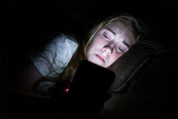 Depressed girl lying down on a couch in the dark while using her smartphone. The light from the screen is illuminating her face.