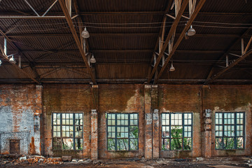 Large broken window in abandoned ruined industrial warehouse or factory building inside, ruins and demolition concept