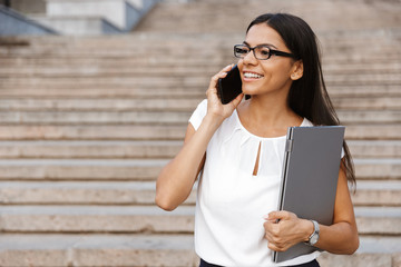 Beautiful business woman walking outdoors talking by mobile phone.