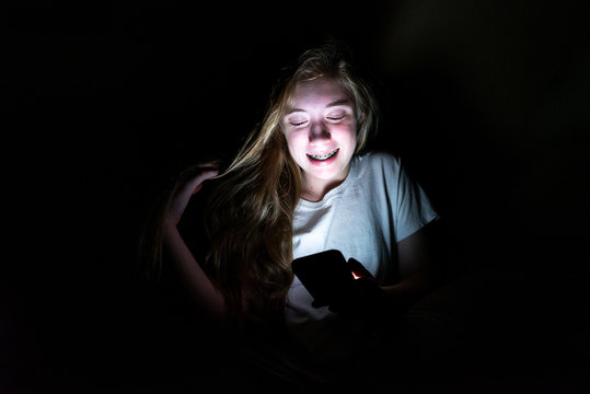 Happy girl sitting on a couch in the dark while using her smartphone. The light from the screen is illuminating her face.