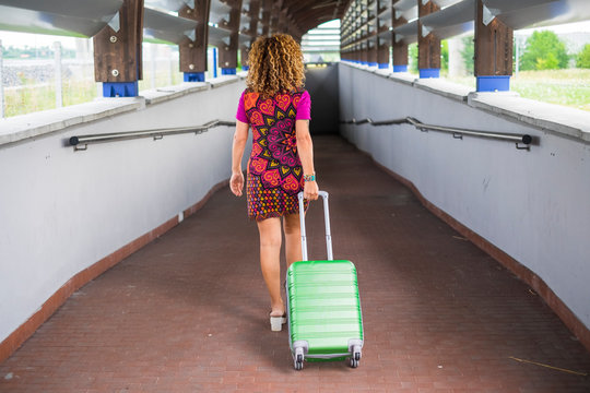 beautiful young curly blonde woman viewed from back rear travel and move walking with a green cabin bag luggage trolley. black dark tunnel in front of her in the background