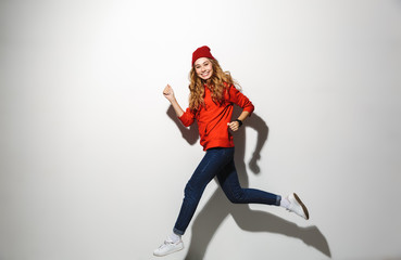 Full length portrait of an excited girl wearing hoodie jumping
