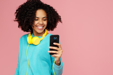Attractive african american young woman with bright smile dressed in casual clothes take picture with smartphone over pink background.