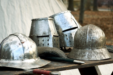 Medieval helmets with eyes slits standing on the table