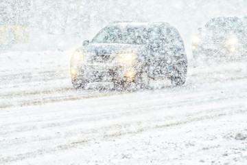 Car rides through a snowstorm. Limited vision on the road. Blizzard - car traffic in bad weather conditions
