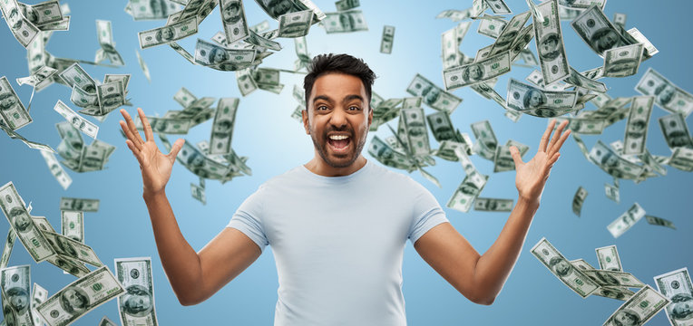 success, wealth and finances concept - happy young indian man celebrating triumph over blue and cash money falling background