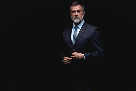 Handsome mature business man isolated on black background