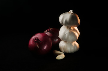Composition of two red onions and three heads of garlic on a black background