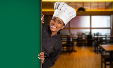 Black Brazilian woman chef cooking looking at camera with green board in wine house blurred background.