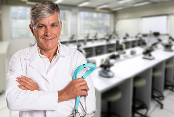 Beautiful smiling doctor man over microscope room background.