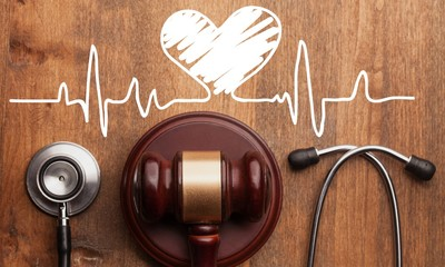 Gavel and stethoscope on wooden background, symbol photo for