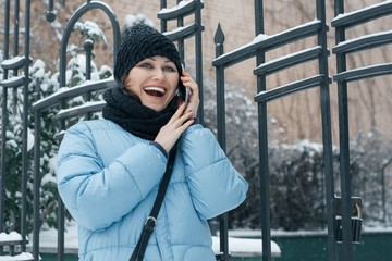 Outdoor winter portrait of mature woman with mobile phone on snowy city street, woman smiling talking.