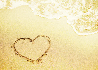 Drawing of heart and sea wave on sand on the seashore, toned. Bright background by St. Valentine's Day, the romantic image