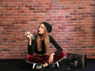 Photo of modern hip hop girl, sitting on floor against brick wall with boombox and spray paint