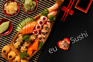Japanese food combo in black background.itten I love Sushi in portuguese. Top view