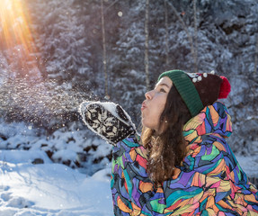 Beauty Winter Girl Blowing Snow in frosty winter Park. Outdoors. Flying Snowflakes. Sunny day. Backlit. Joyful Beauty young woman Having Fun in Winter Park.