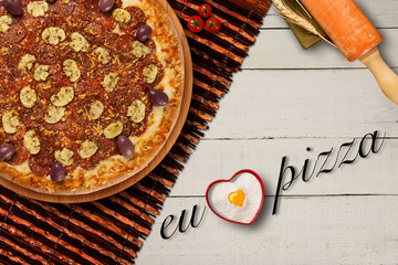 hot homemade brazilian pizza on wood table, top view. I love pizza written in Portuguese. Copy space
