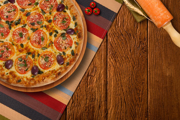 hot homemade Italian pizza margherita with mozzarella and tomatoes on wooden table, top view, copy space