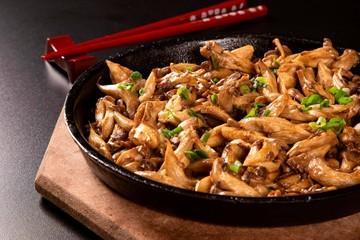 shimeji mushrooms in iron pan in a black background.