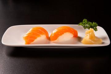 Sake - nigiri sushi with raw salmon on black background