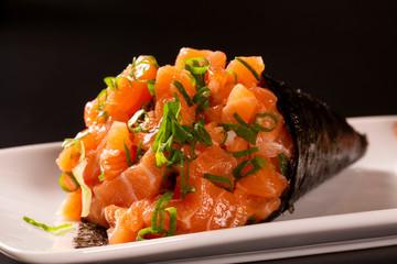 Salmon temaki sushi on white plate in black background.