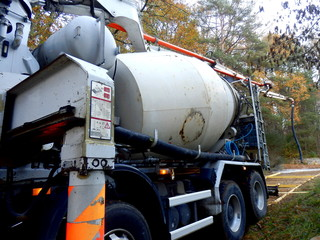 Cement mixer lorry with extendable arm in position to commence cement pouring
