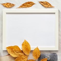 Autumn composition background. Artist home office desk workspace, frame, autumn leaves. Flat lay, top view creative minimal mock up template. Copy space..