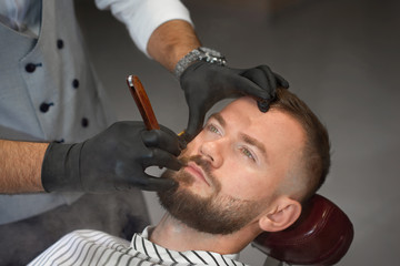 View from above of man on chair while barber shaving beard