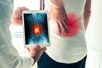 Doctor holding a digital tablet with x-ray-of back pain of a patient