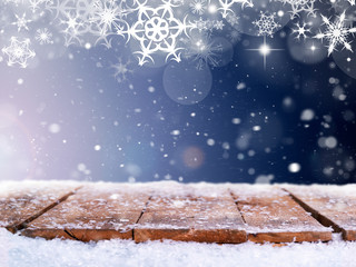 A wooden table top with a snowy white and blue Christmas scene with space for text and product shots.
