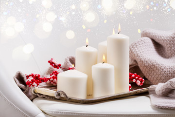 Four white burning advent candles with red berries and knitted blanket on chair with bokeh lights