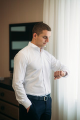 Handsome groom look at the watch in wedding day