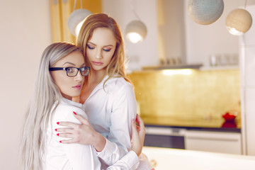 Young sensual female couple holding each other in kitchen