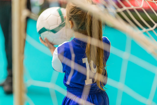 kids in blue teams train and play football in the hall. girls and boys play together soccer.