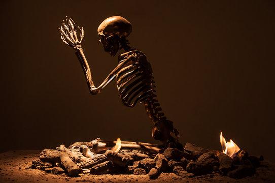 Taksim, Istanbul/Turkey - February 8, 2014: Human skeleton praying on fire. Made by marc quinn