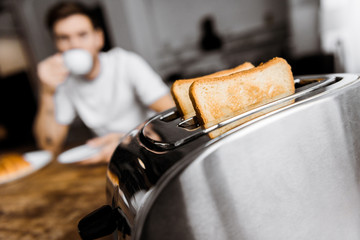 young man drinking coffee at home with toaster on foreground