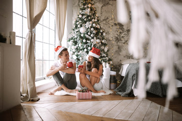 Guy and girl in white t-shirts and Santa Claus hats sit with red cups on the floor in front of the window next to the New Year tree, gifts and candles