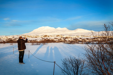 Man photographing with his camera phone snow covered mounts, Iceland on a sunny winters day