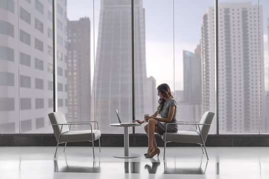 Solo business person working via laptop, internet, virtual, independent, with buildings in background