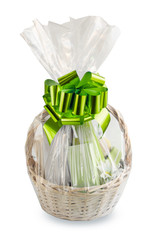 gift basket, hamper packed in transparent paper with a big green bow isolated on a white background